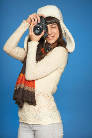 Woman photographer looking through the photo camera viewfinder at you, over blue  photo