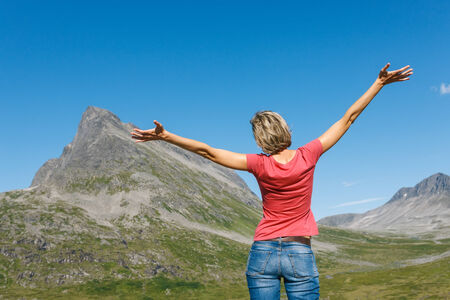 outspread: Back view of happy woman enjoying freedom with arms outspread enjoying peace, serenity in nature outdoors, in top of mountains, Norway