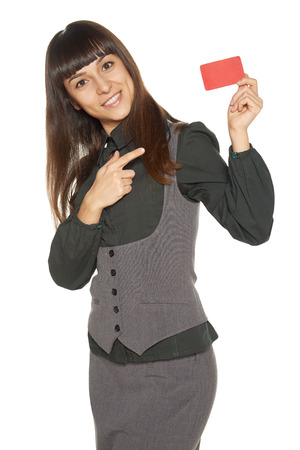Smiling business woman holding credit card pointing at it, isolated on white background photo