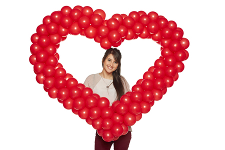 Love concept. Smiling woman holding red balloon heart isolated on white background.  Cute beautiful young woman in love. Stock Photo - 25370027