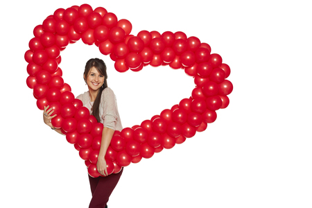 Love concept. Smiling woman holding red balloon heart isolated on white background.  Cute beautiful young woman in love. Stock Photo - 25370045