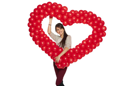 Love concept. Smiling woman holding red balloon heart isolated on white background.  Cute beautiful young woman in love. Stock Photo - 25370046