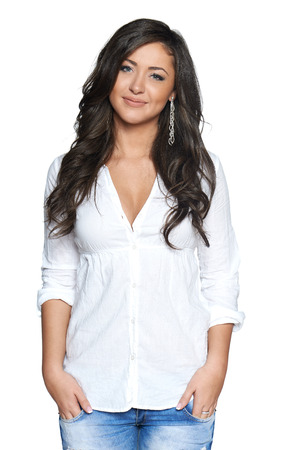 Carefree beautiful happy woman in jeans and white shirt standing with hands in pockets