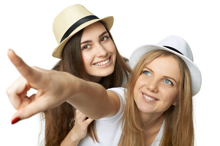 2 persons only: Two women friends having fun. Two happy girls in straw hats and white tshirts smiling and pointing to the side, against white