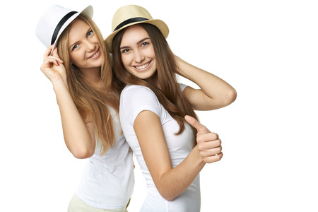 Two women friends having fun. Two happy girls in straw hats and white tshirts smiling and showing thumb up gesture against white  Stock Photo