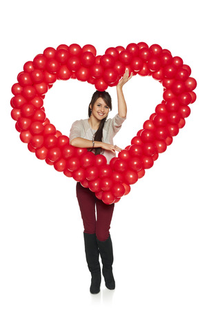 Love concept. Full length smiling woman holding red balloon heart isolated on white .  Cute beautiful young woman in love. Stock Photo - 25650651