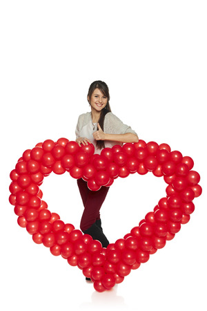 Love concept. Full length smiling woman holding red balloon heart isolated on white background.  Cute young woman in love. Stock Photo - 25650655