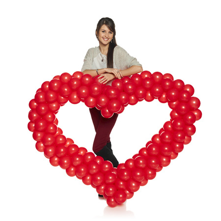 Love concept. Full length smiling woman holding red balloon heart isolated on white background.  Cute young woman in love. Stock Photo - 25650657