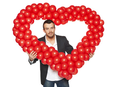 Love concept. Closeup of handsome man peeping through the heart shape formed of d balloons, isolated on white . Stock Photo - 25650748