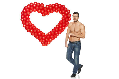 Love concept. Full length handsome shirtless man showing heart shape formed of balloons, isolated on white . photo