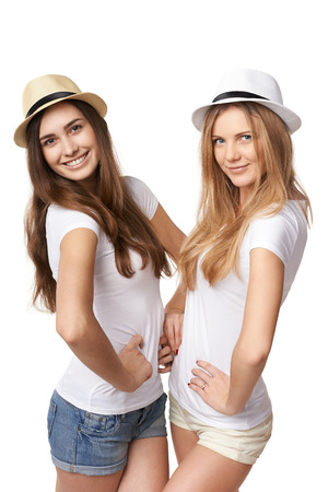 only 2 people: Two women friends having fun. Two happy girls in straw hats and white t shirts posing against white  Stock Photo