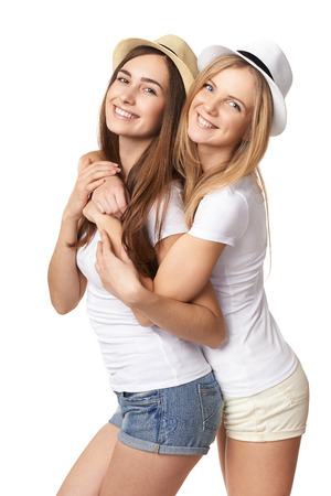 Two women friends having fun. Two happy girls in straw hats and white t shirts hugging and smiling against white