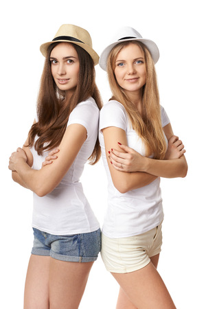 Leaning on each other. Two happy girls in straw hats and white t shirts standing back to back, against white  photo