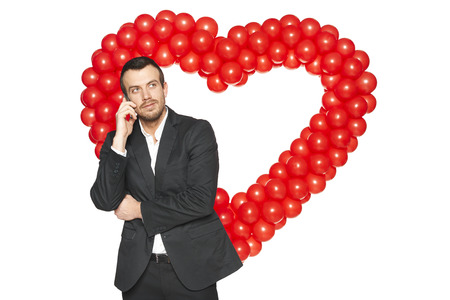 Handsome businessman talking on phone against heart shape formed of d balloons photo