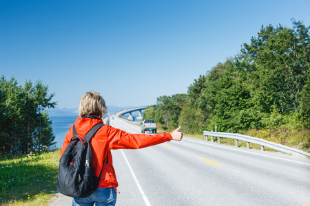 hitch hiker: Hitchhiking travel woman at the route Stock Photo
