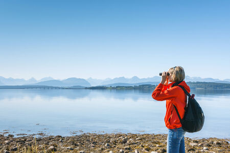 Woman tourist looking through binoculars at distant Atlantic Road, Norway, enjoying landscape photo
