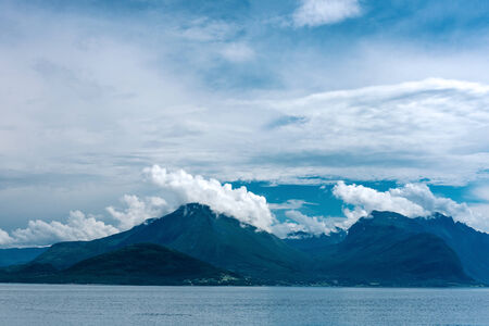 scandinavian landscape: Norway  Fjord scene with hazy mountains and  cloudy sky in a overcast day