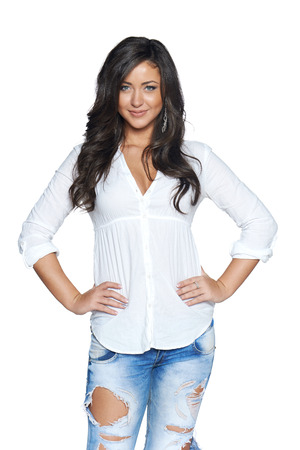 Carefree beautiful happy woman in jeans and white shirt posing over white background photo