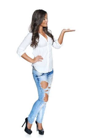 Full length of funky and stylish young woman in jeans and white shirt holding blank copy space on her open palm, over white background