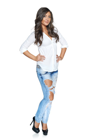 Full body of carefree beautiful happy woman in jeans and white shirt posing over white background photo