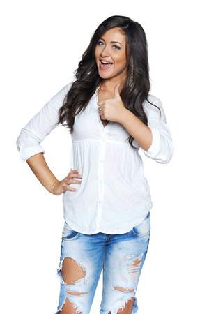 thumbs up sign: Happy young woman in funky ragged jeans and white shirt showing thumb up sign isolated on white background