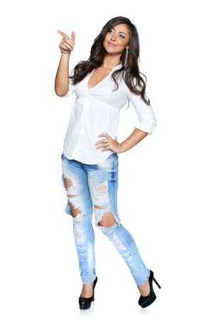 Full length young woman in funky ragged jeans and white shirt pointing to the side, isolated on white background photo