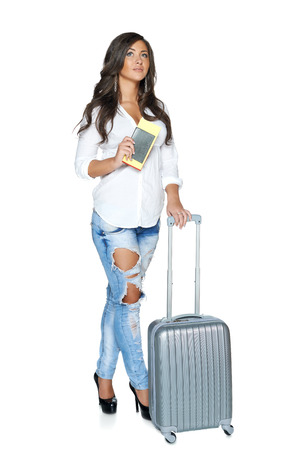 Full length of pensive young female with travel suitcase and tickets looking up, isolated on white background photo