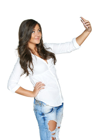 Happy young girl taking pictures of herself through cellphone, over white background photo