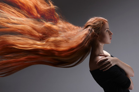 Beautiful red headed woman with long hair flying against gray background, side view photo