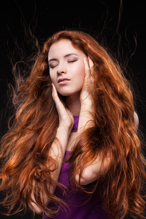 Beautiful red headed woman with long hair over dark background Banque d'images