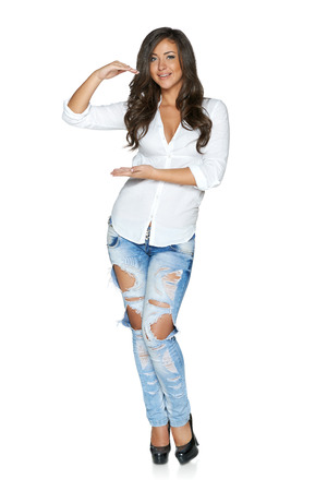 Full body of carefree beautiful happy woman in ragged jeans and white shirt holding blank space between hands, over white background photo
