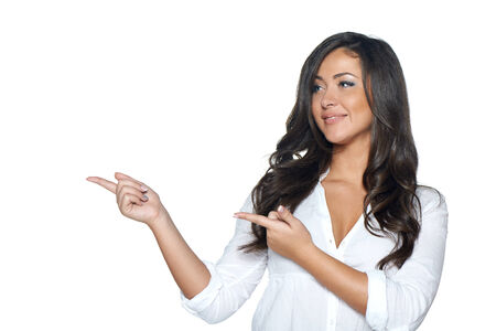 Stylish young woman in white shirt holding blank copy space and pointing at it, on her open palm, over white background photo