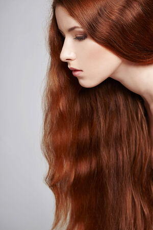 Closeup of beautiful red headed woman, over gray background photo