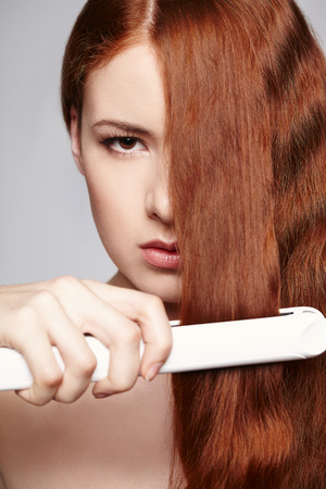 Hairstyling  Beautiful redheaded woman with hair straightening irons Stock Photo