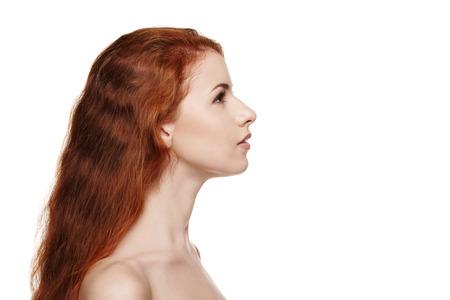 perfil de mujer rostro: Vista lateral cerca de la hermosa mujer pelirroja mirando hacia adelante sobre fondo blanco