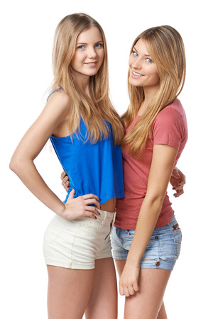 only women: Two girls friends standing against white background Stock Photo