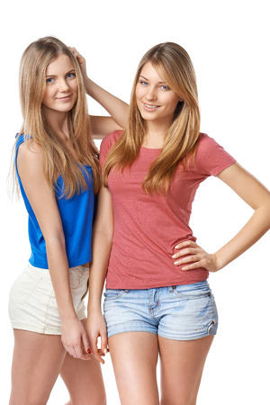 standing against: Two girls friends standing against white background Stock Photo