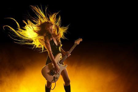 concierto de rock: Muchacha joven atractiva de la roca que toca la guitarra eléctrica Foto de archivo