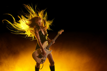 guitarists: Young attractive rock girl playing the electric guitar Stock Photo