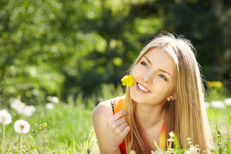 envisioning: Girl lying on field of dandelions while daydreaming in spring