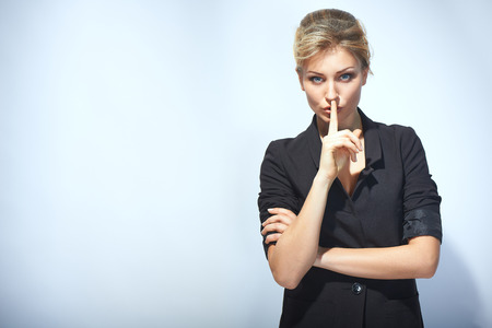 Businesswoman with finger on her lips photo