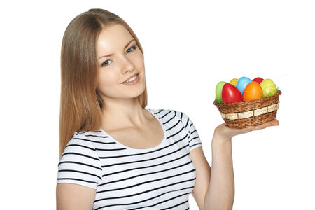 Portrait of beautiful female holding a basket of Easter eggs isolated on white background photo