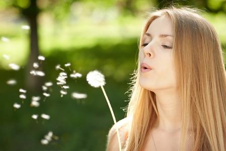 blows: Woman blowing dandelion outdoors.