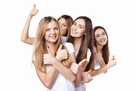 Happy group of friends gesturing thumbs up, over white background photo
