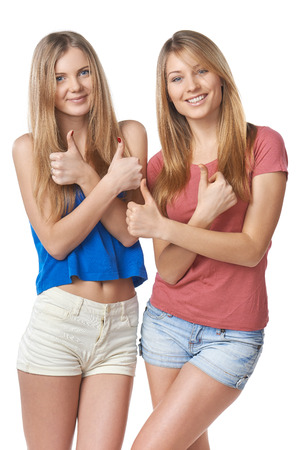 Happy two girl friends gesturing thumbs up, over white background photo