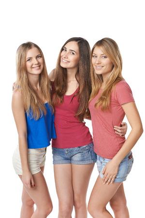 Three happy girls friends standing hugging against white background photo