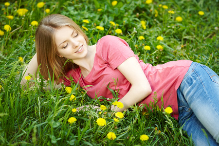 envisioning: Spring girl lying on the field of dandelions