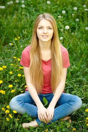 envisioning: Female sitting on the field of dandelions looking up