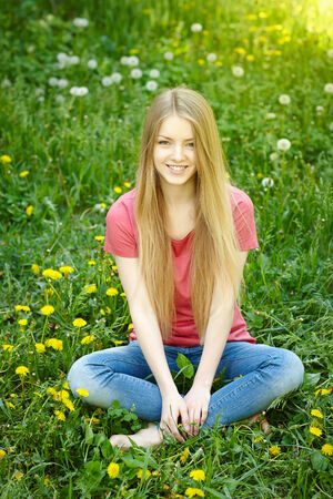 envisioning: Smiling female sitting on the field of dandelions looking at camera, spring female portrait Stock Photo