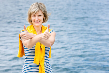 over shoulders: Middle age woman in striped tshirt and yellow pullover over shoulders outdoors gesturing thumb up against sea background Stock Photo